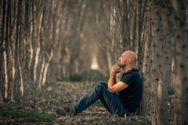 Siedzący mężczyzna z depresją przechodzący przez trudny okres w swoim życiu, cierpiący na psychiczne wyczerpanie, lęk, wypalenie zawodowe, pojęcie opieki zdrowotnej