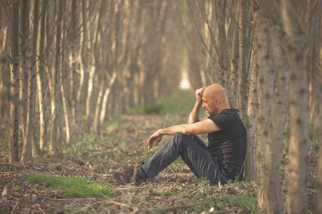 Siedzący mężczyzna z depresją przeżywający trudny okres w swoim życiu, cierpiący na psychiczne wyczerpanie, lęk, wypalenie