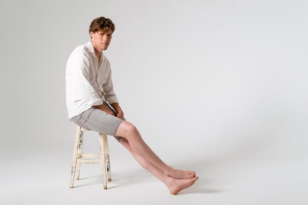 Siedzący na zardzewiałym krześle na całej długości młody przystojny młody mężczyzna ubrany w białą koszulę i szare szorty ze skrzyżowanymi nogami, patrząc z przodu na białym tle na białej ścianie