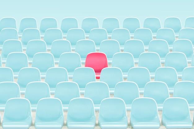 Siedzenie w kolorze czerwonym na środku jasnoniebieskiego krzesła na stadionie.