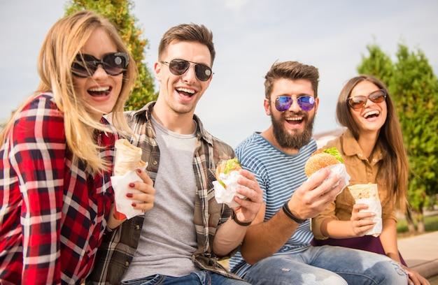 Siedzenie w parku i wspólne jedzenie fast foodów.