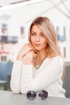 Siedzi atrakcyjna piękna młoda kobieta w vintage sweter z dzianiny o niebieskich oczach