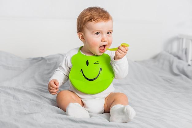 Siedzi dziecko noszące śliniaczek