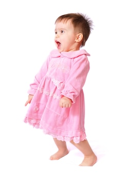 Siedzi śmiejąc się całkiem mała roczna dziewczynka z otwartymi ustami w różowej sukience zabawy trzymając palec u nogi