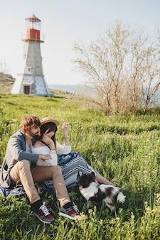 Siedzi w trawie młoda stylowa hipster para zakochanych, spacery z psem na wsi, moda boho w stylu letnim, romantyczny