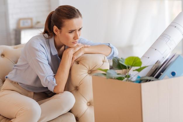 Siedzieć samotnie. spokojny zdenerwowany doświadczony inżynier źle wyglądający, siedząc sam i patrząc na pudełko z rzeczami osobistymi z poprzedniego miejsca pracy