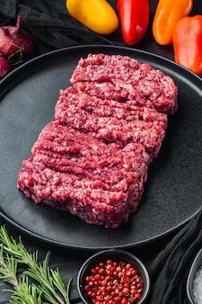 Siekać. mięso mielone z składników do gotowania, na tle czarny drewniany stół