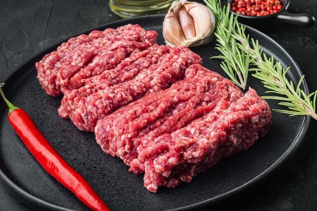 Siekać. mięso mielone ze składnikami do gotowania, na czarnym tle
