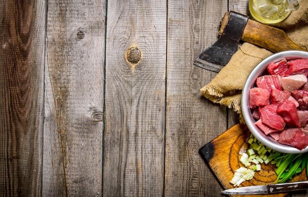 Siekane surowe mięso ze świeżą cebulą i siekierą na starym materiale.