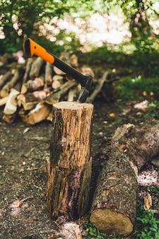 Siekiera do cięcia drewna. zbliżenie siekiery tnącej kłodę, podczas gdy inne kłody leżą w tle.