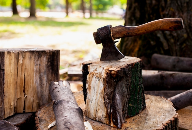 Siekiera utknęła w drewnianej kłodzie