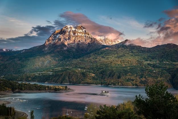 Sielankowe ujęcie ogromnej góry pokrytej roślinnością, u podstawy której znajduje się zbiornik wodny