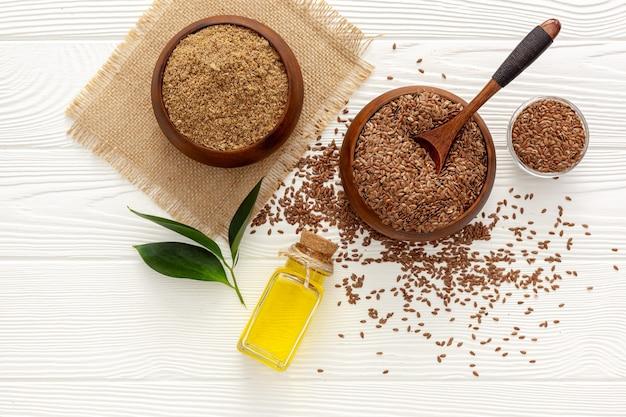 Siemię lniane w łyżce i misce z butelką oleju lnianego i mąki lnianej