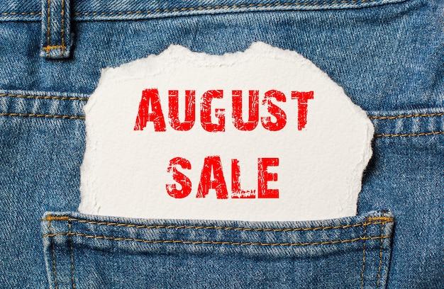 Sierpniowa wyprzedaż na białym papierze w kieszeni niebieskich dżinsów