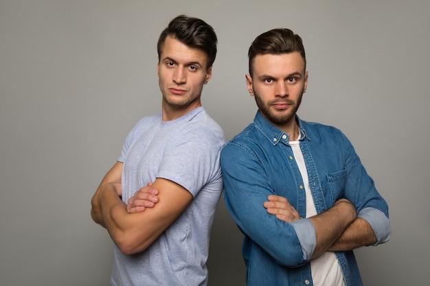 Siła braci. dwaj młodzi mężczyźni w zwykłych ubraniach stoją plecami do siebie z wesołymi wyrazami twarzy, pozują z założonymi rękami i uśmiechają się do kamery.