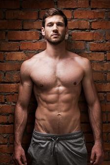 Siła i męskość. przystojny młody muskularny mężczyzna pozuje stojąc przy ścianie z cegły