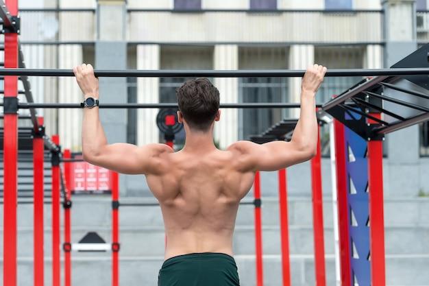 Siła i motywacja muskularny i silny facet ćwiczący młody sportowiec podciąga się