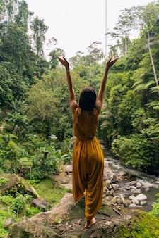 Siła natury. zadowolona dziewczyna podnosząca ręce oddychając czystym powietrzem i ciesząc się tropikalnym klimatem