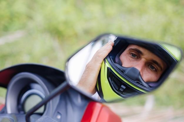 Siłacz na polu tropikalnej dżungli z czerwonym motocyklem