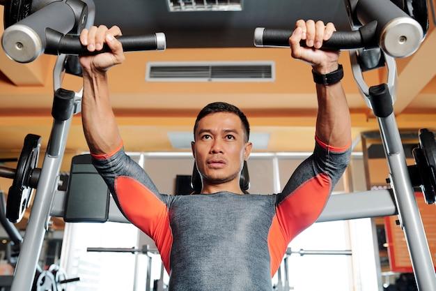 Siłacz robi ćwiczenia klatki piersiowej