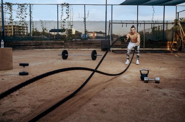Siłacz robi ćwiczenia z linami