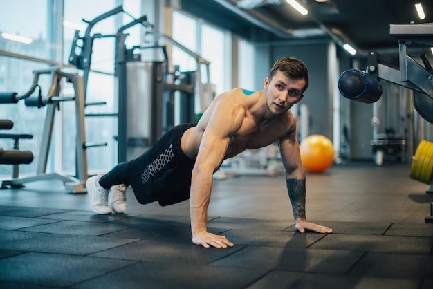 Siłacz z nagi tors robi pompki na siłowni