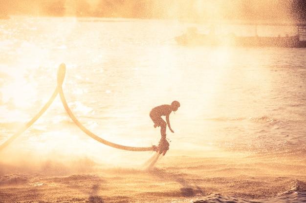 Silhouette i rocznika koloru styl pokazano flyboard na rzece chaophya
