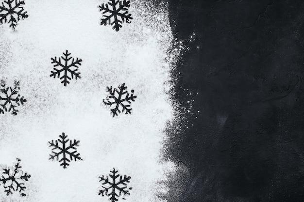 Silhouettes płatki śniegu wykonane z mąki na czarnej przestrzeni kopii.