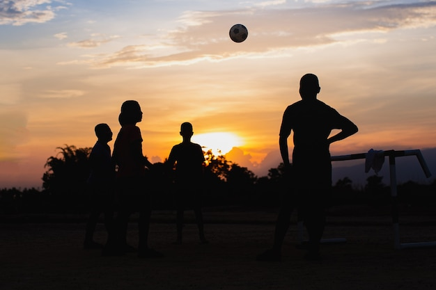 Silhuoette sport akcji na świeżym powietrzu grupy dzieci bawiących się w piłkę nożną uliczną