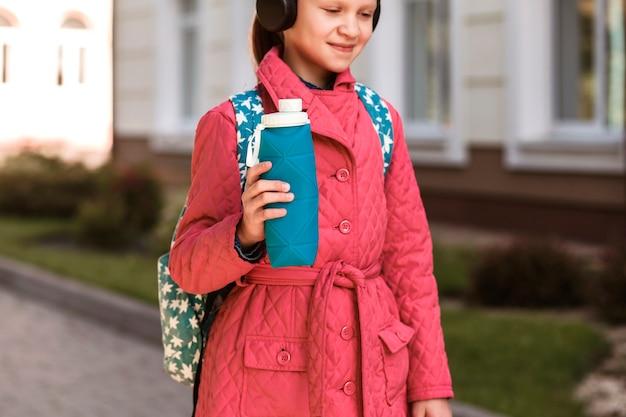 Silikonowa butelka wielokrotnego użytku w rękach małej dziewczynki na tle miasta