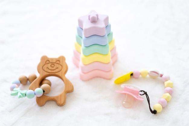 Silikonowa piramidka i gryzaki do zębów o pięknych kolorach na białym tle