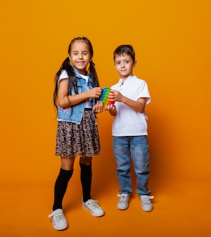 Silikonowa zabawka antystresowa z przyciskiem. dzieci bawią się pop to na żółtym tle.
