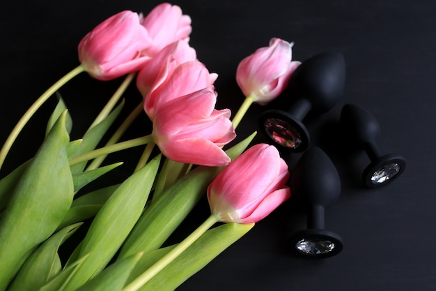 Silikonowe czarne dildo i różowe tulipany