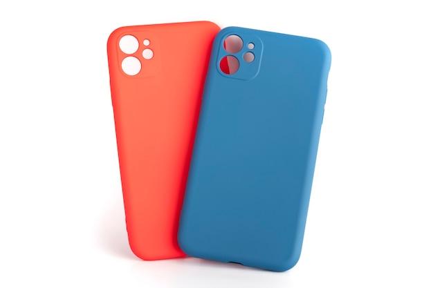 Silikonowe etui na smartfony w kolorze czerwonym i niebieskim na białym tle. akcesoria do telefonów komórkowych