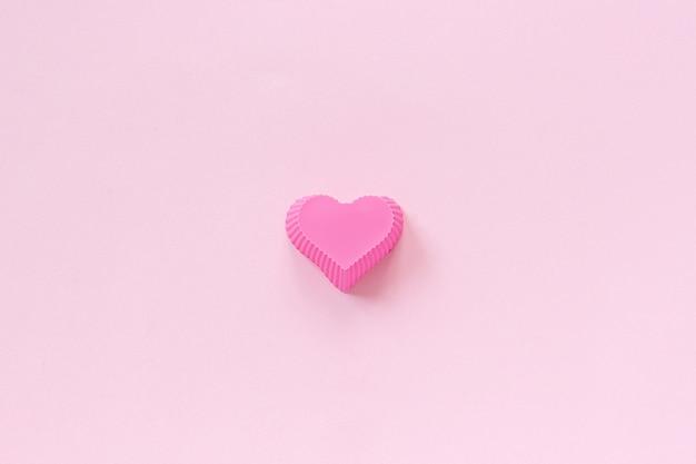 Silikonowe naczynie w kształcie serca do pieczenia babeczek na różowym tle papieru.