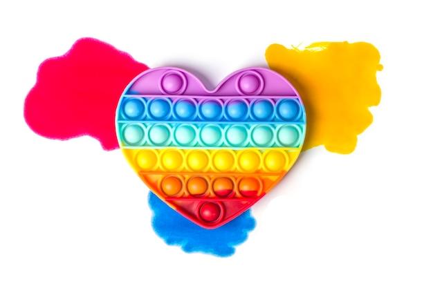 Silikonowe tęczowe serce na jasnych plamach farby.