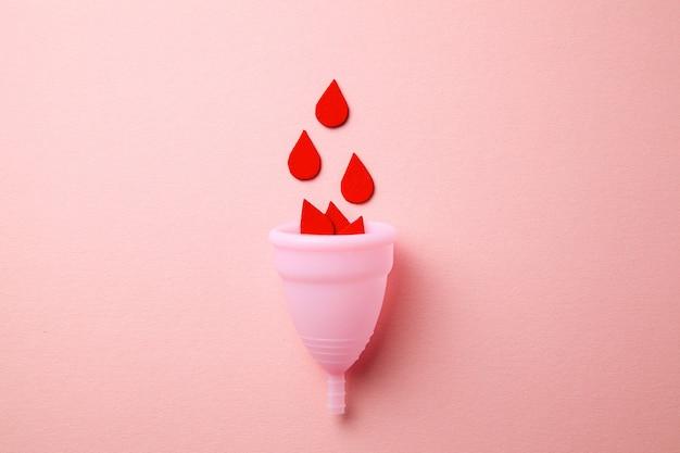 Silikonowy kubek menstruacyjny z papierowymi kroplami krwi