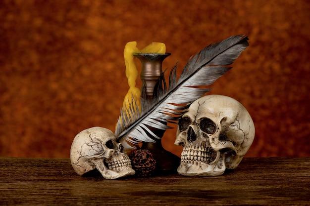 Sill życie z czaszkami, starymi świecami i piórami na tle starej płyty żelaznej.
