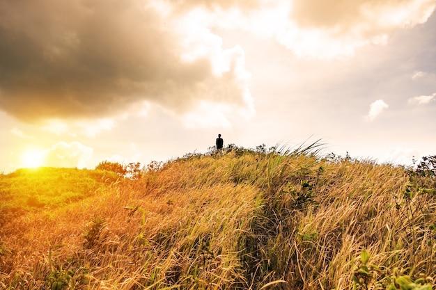 Sillouette człowiek stoi na szczycie górskiej łąki złoty błyszczący