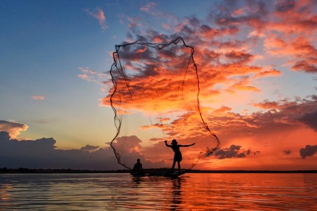 Silluate rybak i łódź w rzece podczas zachodu słońca, rybak rzucający sieci podczas zachodu słońca, podczas zachodu słońca, tajlandia