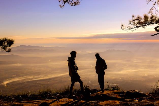 Silluate tow man podnieść rękę i stojąc podczas zachodu słońca na szczycie góry