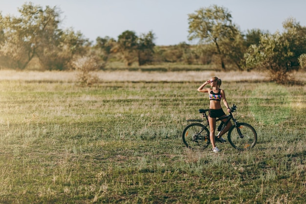 Silna blondynka w kolorowym garniturze siada na rowerze na pustynnym terenie porośniętym drzewami i zieloną trawą i patrzy w słońce. koncepcja fitness.