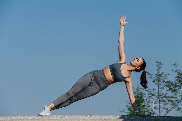 Silna brunetka ćwicząca na świeżym powietrzu stojąc na boku