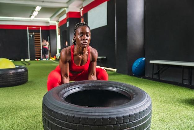 Silna czarna atletka na siłowni wykonująca ćwiczenia podnoszenia kół w celu wzmocnienia mięśnia czworogłowego i bicepsa w czerwonej odzieży sportowej