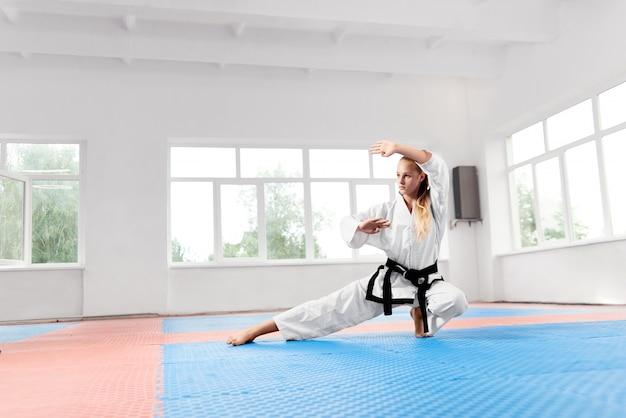 Silna dziewczyna ubrana w białe kimono z czarnym pasem ćwiczącym karate.