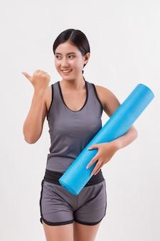 Silna elastyczna kobieta jogi fitness z matą do jogi
