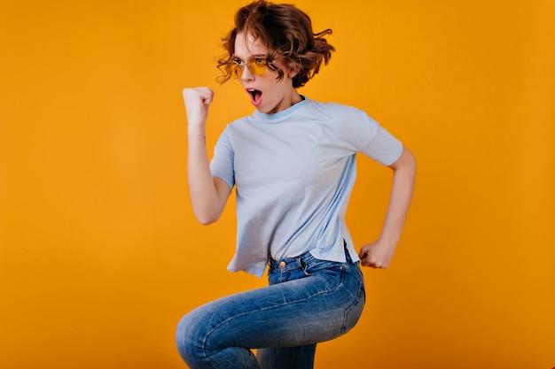 Silna entuzjastyczna dziewczyna w niebieskiej koszulce skacząca na żółtej przestrzeni