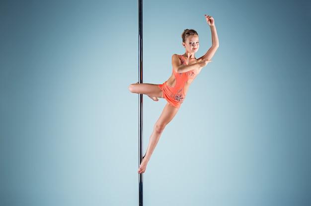 Silna i pełna wdzięku młoda dziewczyna wykonująca ćwiczenia akrobatyczne na pylonie