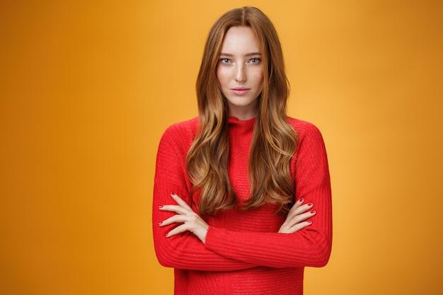 Silna i pewna siebie, atrakcyjna stylowa rudowłosa kobieta o odważnym spojrzeniu i pewnym siebie, trzymająca ręce skrzyżowane nad ciałem, patrząca skupiona na kamerę na pomarańczowym tle