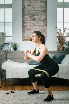 Silna i piękna dziewczyna fitness sportowy w odzieży sportowej robi przysiady z opaskami sportowymi